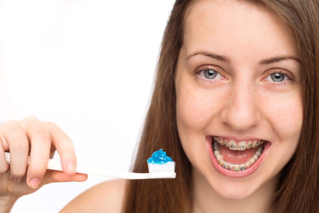 Smiling girl with braces holding toothbrush morning hygiene isolated