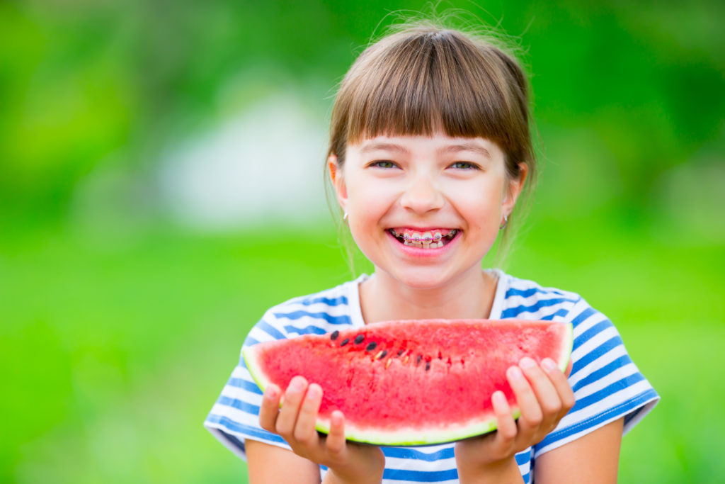 smiling girl with braces eating watermelon